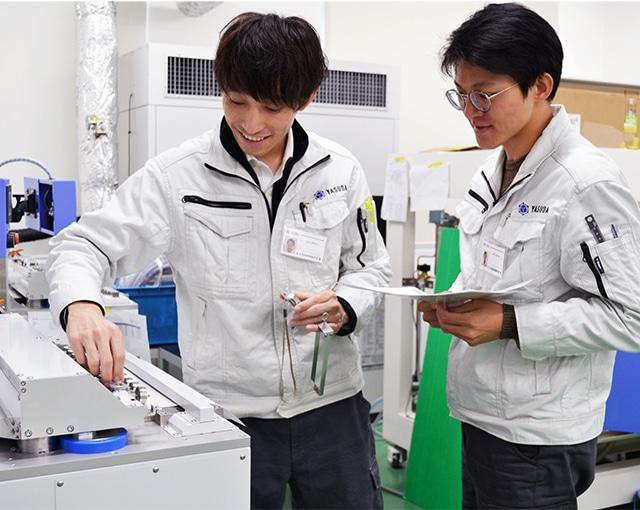 機器の案内をする安田精機製作所の社員